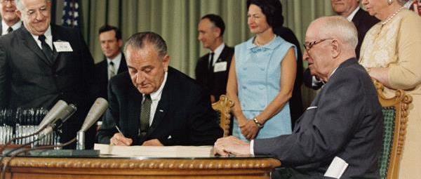 President Lyndon B. Johnson signing the Medicare Bill into law on July 30th, 1965