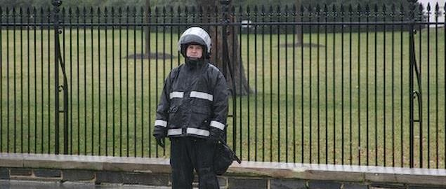A Uniformed US Secret Service Agent stands guard in riot gear outside the White House