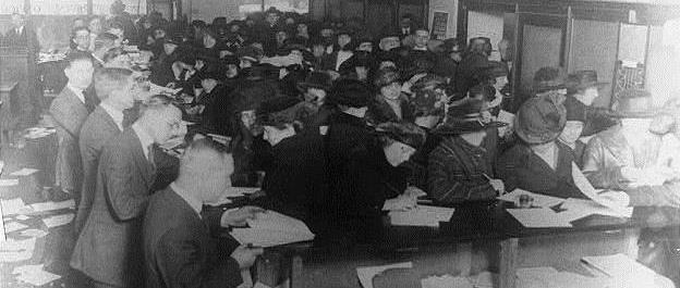 Group of Americans filling out their tax forms in the 1920's